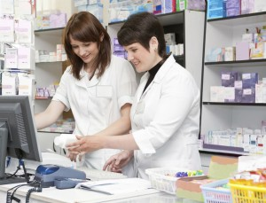 An experienced pharmacist shows a young pre-reg the system.